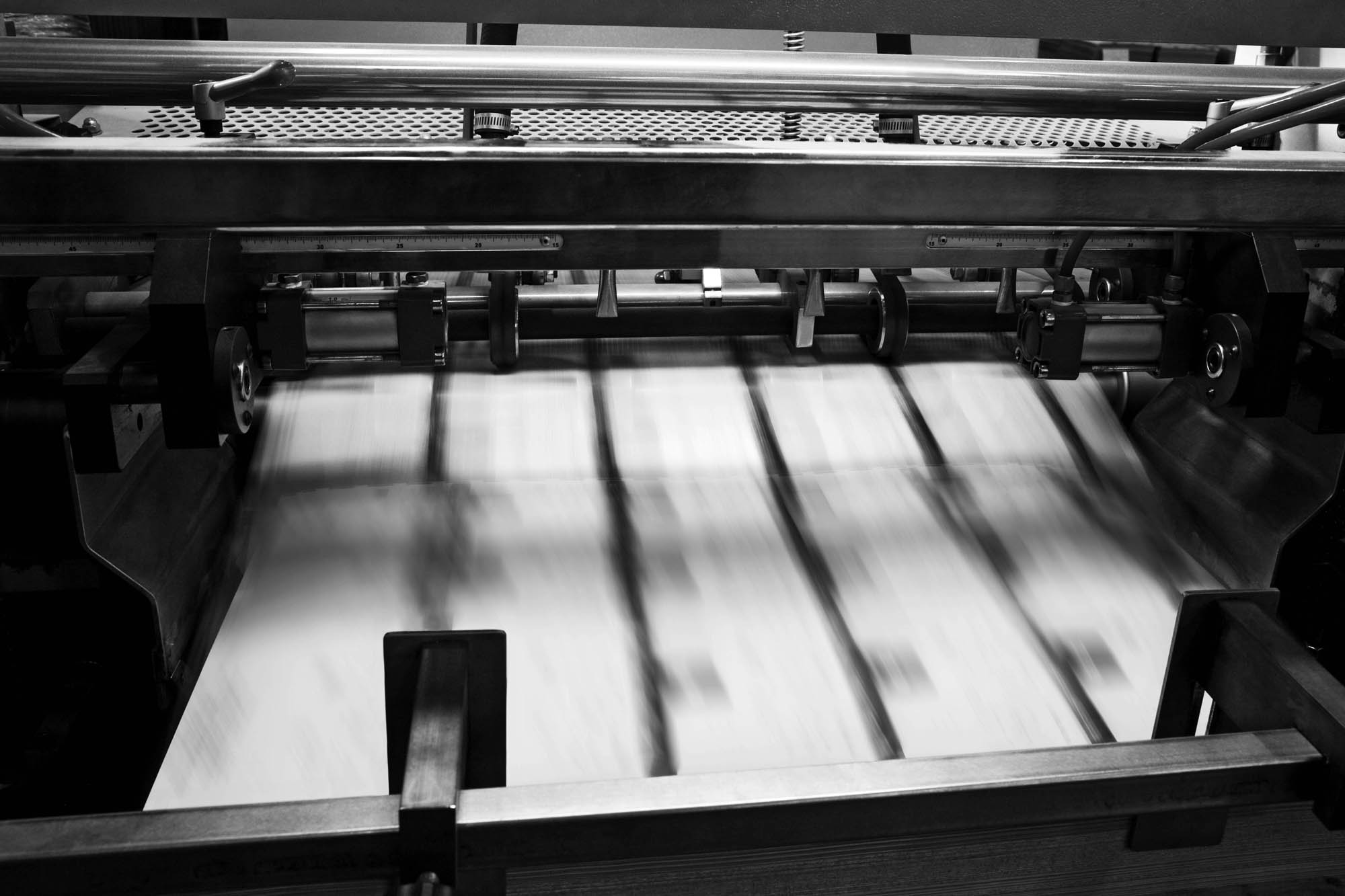 Black and white photo of an offset printer producing direct mail marketing flyers