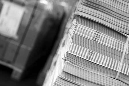 Black and white photo of a stack of printed booklets for distribution